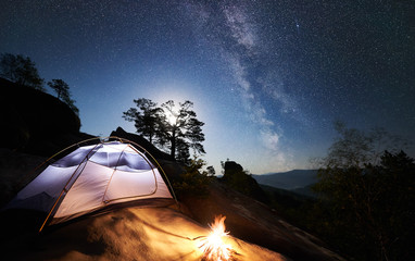 Tourist camping at summer night on rocky mountain. Glowing tent and campfire under amazing night sky full of stars and Milky way. On the background beautiful starry sky, big boulders and trees