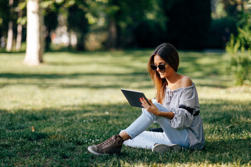 Young woman using a digital tablet in the park