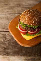Tasty burger with cheese on wooden table