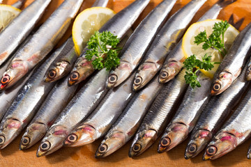 Anchovies served on wooden surface
