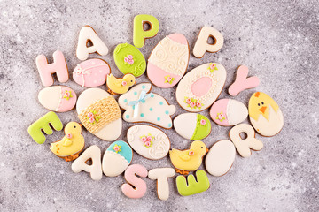 Happy Easter colorful lettering Happy Easter of ginger biscuits and cookies bunny on stone background.