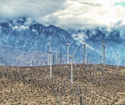 Environmental green power windmills dot a hill in the desert.