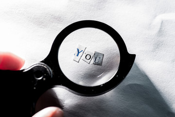 """finding yourself. Word """"you"""" of letters on paper through a magnifying glass"""