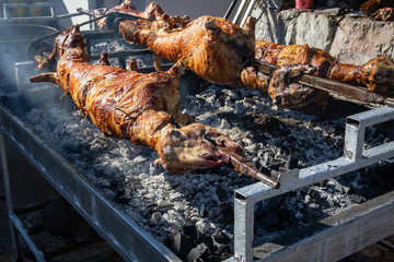 Whole lambs baked on a spit, direct on fire outdoor