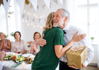 Young woman giving a gift to her grandfather on indoor party, hugging.
