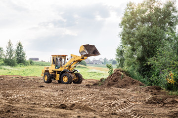 large yellow wheel loader aligns a piece of land for a new building Fototapete