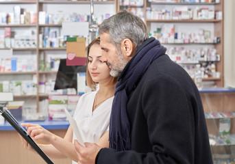 Drugstore specialist showing folder to customer.