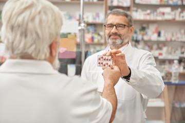 Pensioner taking blister pack from pharmacist.