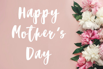 Happy Mother's Day text sign on peonies flat lay. Pink and white peonies border on pastel pink paper with space for text.  Stylish floral greeting card.