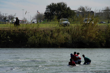 Migrants try to cross the Rio Bravo towards the United States, seen from Piedras Negras