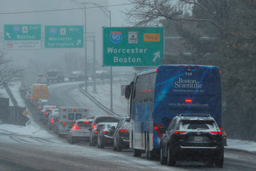 Vehicles back up on an onramp to the Massachusetts Turnpike during a winter snow storm in Boston