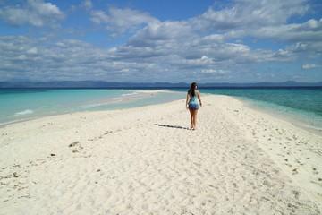 woman strolling on a tropical white beach