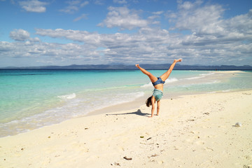 young woman doing a handstand on the beach