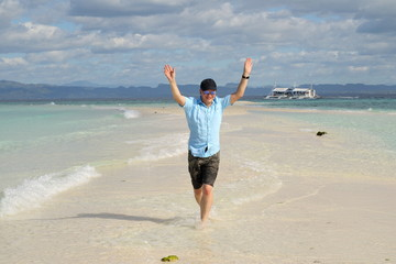 man walking on the beach with raised arms and happy face