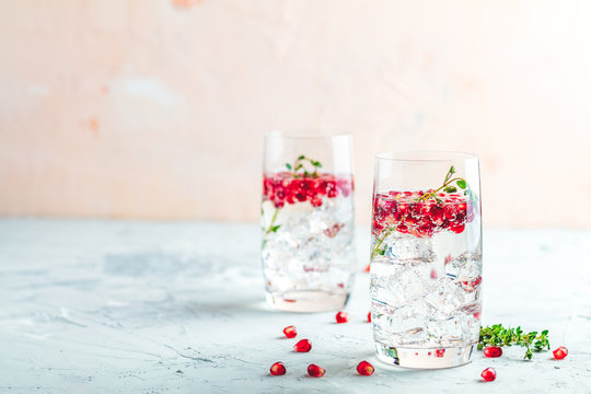 Festive drinks, gin and tonic pomegranate cocktail or detox water with ice