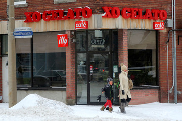 A woman and boy pass by a closed ice-cream shop during a snowstorm in Toronto
