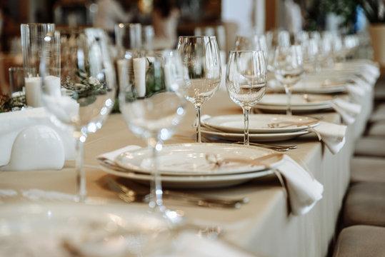 Festive table setting. Glasses, plates, cutlery, napkins. Defocus