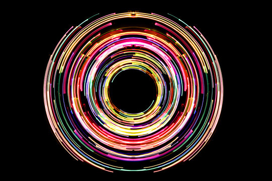 Abstract neon circle lines with empty copy space inside isolated on black background. Colorful led lights long exposure rotation photo.