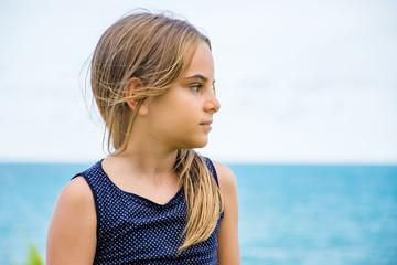 Criança modelo sentada em frente ao mar azul