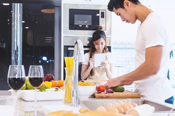 Beautiful asian young couple loving smiling is looking to cooking in kitchen at home.