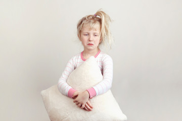 No sleeping insomnia concept. Cute funny adorable sad unhappy  blonde Caucasian girl child embraces holding white soft fluffy pillow. Kid does not want to sleep and refuses to go to bed