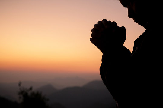 Silhouette of girl praying over beautiful sky background. Christian Religion concept background. fighting and victory for god