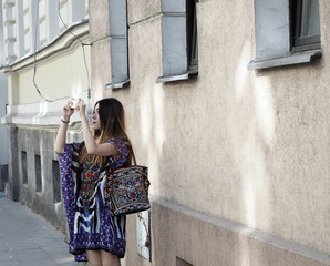 An Asian stylist young tourist woman is taking photo, travel blogger on a street in old city town.