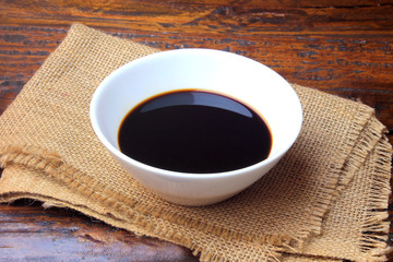 dark soy sauce in a white ceramic bowl isolated on rustic wooden table. Asian cuisine