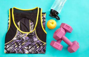 Athlete's set with female clothing, dumbbells and bottle of water on blue background