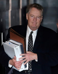 U.S. trade representative Robert Lighthizer holds documents as he and members of the U.S. trade delegation to China leave a hotel in Beijing
