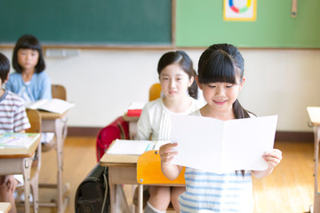 授業中に作文を読む小学生の女の子