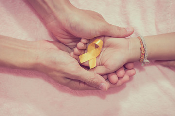 Mature hands and boys cancer surgery symbol ribbon, view from above.