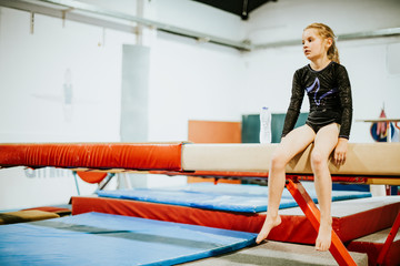Young gymnast sitting on a balance beam