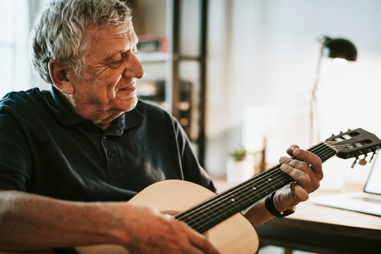 Senior man playing on his guitar