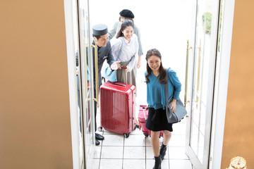 ホテルに入る3人の女性旅行者