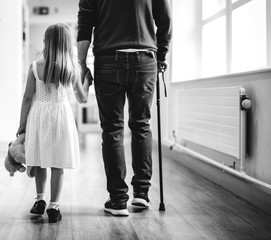 Daughter walking with her disabled father