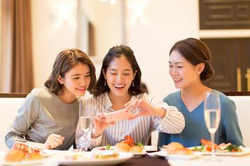 スマートフォンで料理を撮る3人の女性