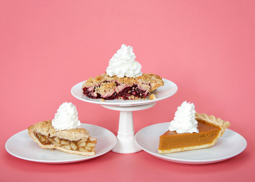 Apple and pumpkin pie on plates with whipped cream, cherry pie on plate with whipped cream on pedestal above them. Pink background. National pie day march 14