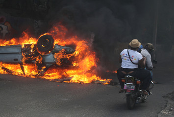 People on a motorcycle ride near a burning car during anti-government protests in Port-au-Prince