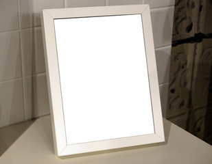 Mock up blank Image of a white vertical portrait  photo frame mockup on a table.