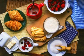 fresh breakfast foods. milk yogurt, croissants and frozen berries.