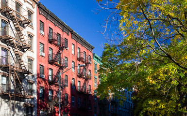 Tree lined street with old historic apartment buildings in the East Village neighborhood of New York City NYC