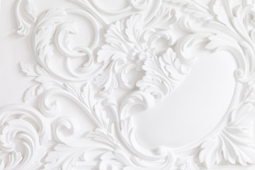 Beautiful ornate white decorative plaster mouldings in studio. The white wall is decorated with exquisite elements of plaster stucco
