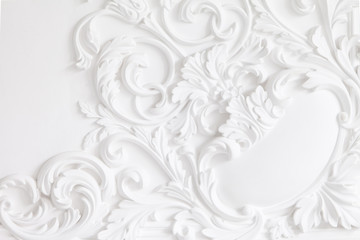 Beautiful ornate white decorative plaster mouldings in studio. The white wall is decorated with exquisite elements of plaster stucco Wall mural