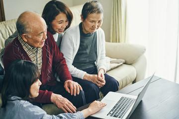 ノートパソコンでインターネットをする家族