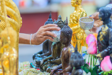 Close up hand of Thai people while bathing rite to buddha images in Songkran festival on the April 13 annual ritual every year. Buddhist is bathing a Buddha statue to gain merit during Thai New Year.