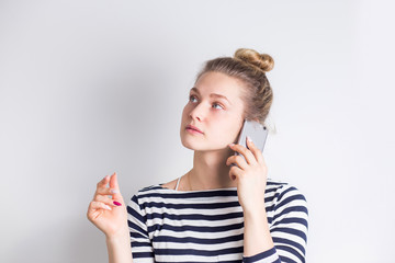 Portrait of a casual woman holding smartphone and talking on the phone over white background