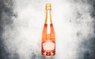 Bottle with pink sparkling wine or rose champagne and glasses, gray background with place for text, holiday or date concept, flat lay, top view