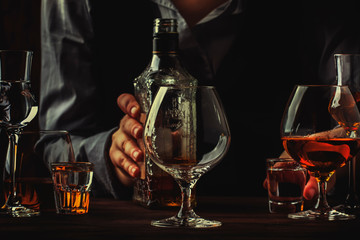 The bartender holding bottle of strong drink in hand and big wine glass on the old bar counter. Vintage wooden background in pub or bar, night mood. Place for text, toning, selective focus