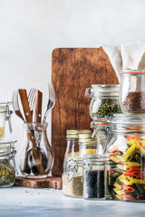 Stocks or set of cereals, pasta, groats, organic legumes and useful seeds in glass jars. Vegan source of protein and energy resources. Healthy vegetarian food. Domestic life scene.